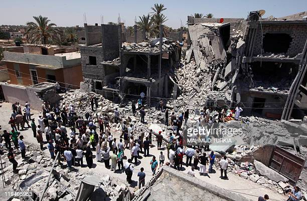 In a picture taken on a governmentguided tour Libyans gather on June 19 2011 next to the rubble of buildings the Libyan authorities said were damaged...