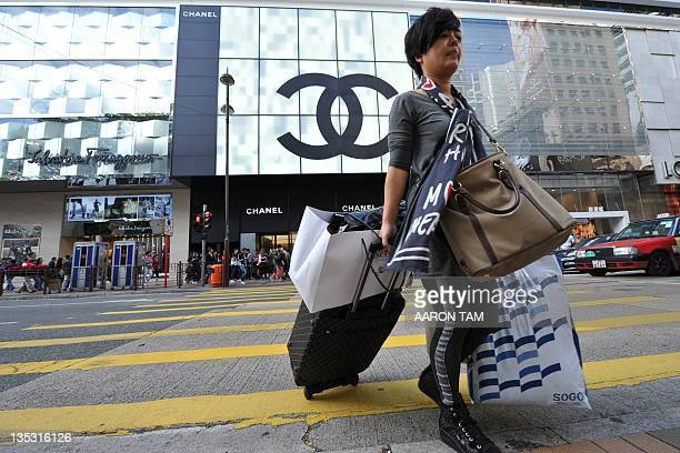 In a picture taken on December 8 a Mainland Chinese tourist crosses the street carrying multiple shopping bags in the Tsim Sha Tsui region of Hong...