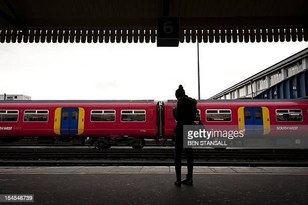 In a picture taken on January 19 2012 a rail passenger waits for a train on the platform at Clapham Junction train station in south London Delays in...