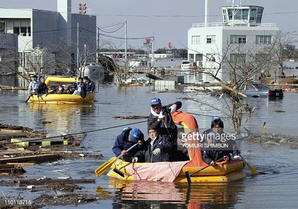 In a picture taken on March 12 2011 people evacuate from the flooded airport terminal building of Sendai airport with rubber boats at Natori city in...