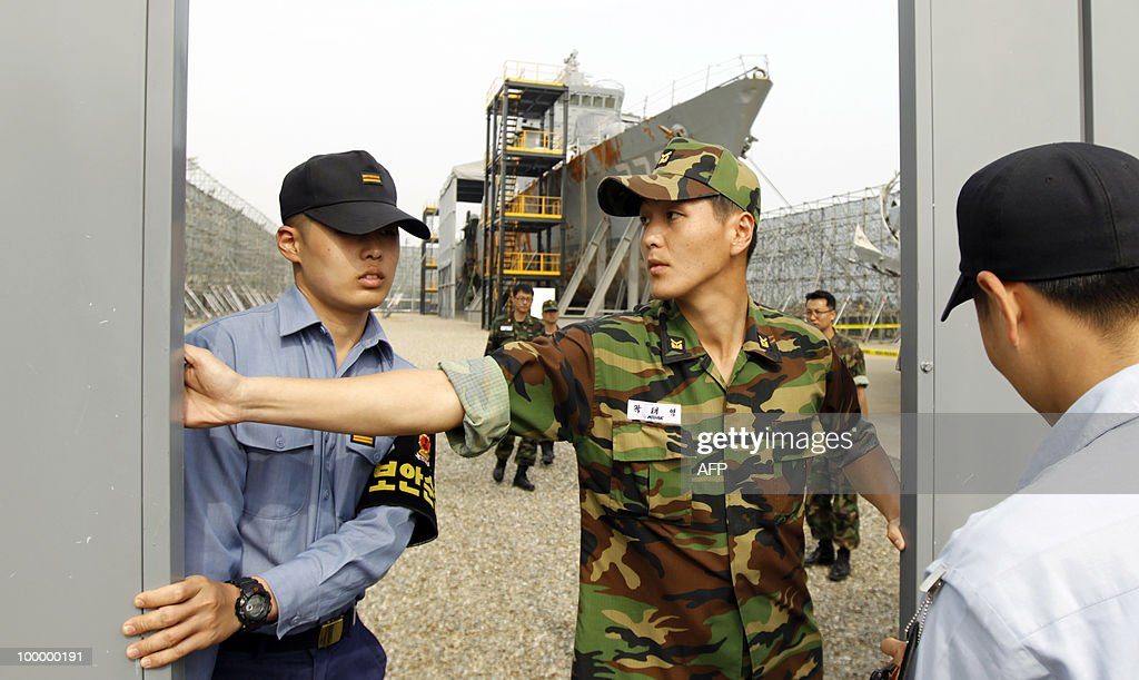 In a picture taken on May 19, 2010, Navy officers close the gate to the area where the salvaged South Korean naval vessel Cheonan, which sank on March 26 near the maritime border with North Korea, is kept during a media briefing at the Second Fleet Command of Navy in Pyeongtaek, south of Seoul. A torpedo fired by a North Korean submarine sank a South Korean warship with the loss of 46 lives, investigators said on May 20, 2010.