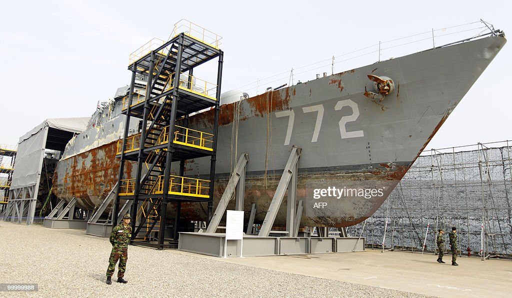 In a picture taken on May 19, 2010, South Korean navy personnel stand guard next to the wreckage of the salvaged naval vessel Cheonan, which sank on March 26 near the maritime border with North Korea, during a media briefing at the Second Fleet Command of Navy in Pyeongtaek, south of Seoul. A torpedo fired by a North Korean submarine sank a South Korean warship with the loss of 46 lives, investigators said on May 20, 2010.