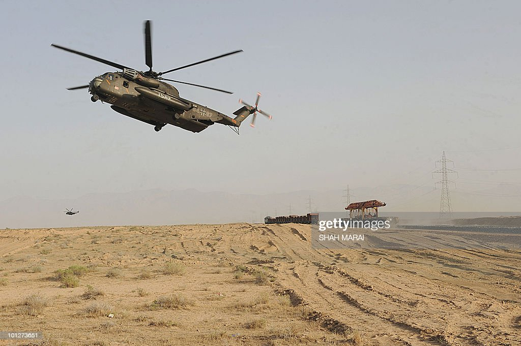 In a picture taken on May 25, 2010 a German helicopter flies over railway track inaugurated in Hairatan. In the harsh desert heat on the northern border with Uzbekistan, workers are hammering down the tracks of Afghanistan's first railway which Afghanistan says is a revolutionary project that could revive the poverty-stricken, war-ravaged, landlocked country's status as a thriving 'silk road' trade hub. AFP PHOTO/SHAH Marai