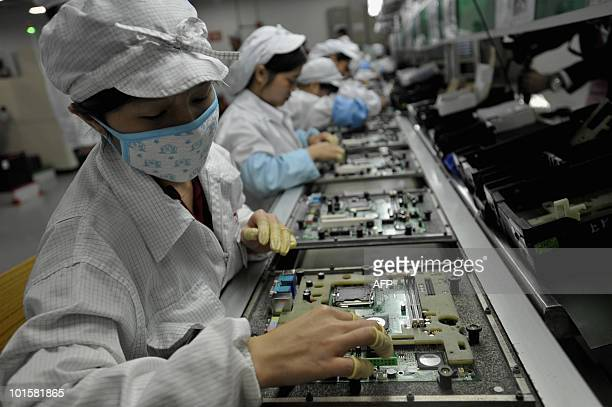 In a picture taken on May 26 2010 Chinese workers assemble electronic components at the Taiwanese technology giant Foxconn's factory in Shenzhen in...