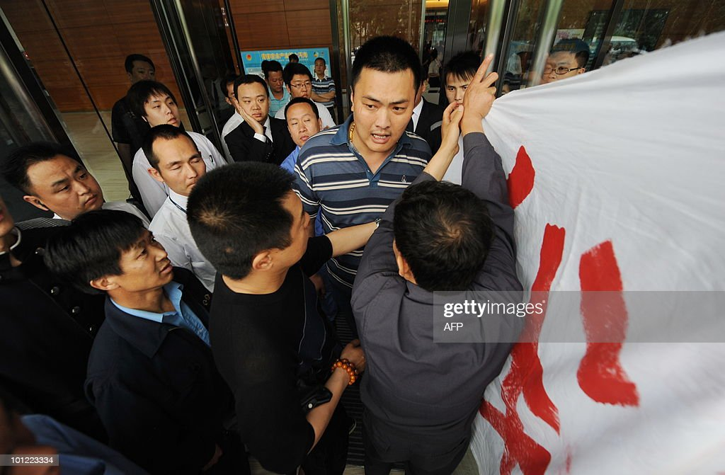 In a picture taken on May 27, 2010 contract labourers hang a banner saying 'We need to survive' as they protest during a labour dispute outside an office in Beijing. China issued new rules making it harder to fire workers recently, in a sign Beijing is seriously concerned about the rising unemployment. CHINA