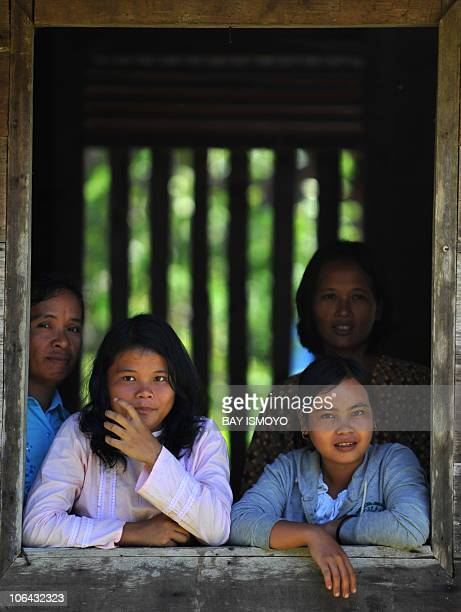 In a picture taken on November 1 2010 villagers watch Indonesian Red Cross workers from the window of a building at Bulasat village in South Pagai in...