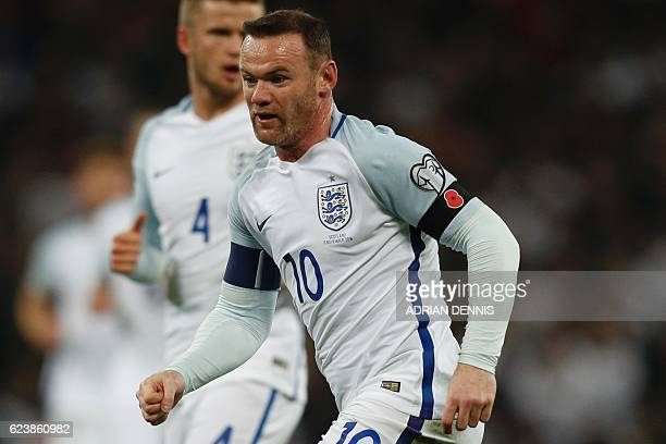 In a picture taken on November 11 2016 England's striker Wayne Rooney wears a poppy armband to commemorate Armistice Day as he plays during a World...