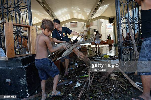 In a picture taken on November 15 volunteers remove debris from the destroyed Santo Nino church in Tacloban city, Leyte province, central...