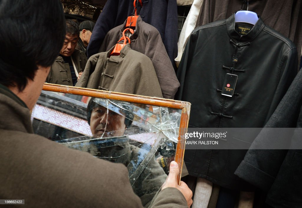 In a picture taken on November 17, 2012, a man looks at himself in a cracked mirror as he tries on a jacket at the Panjiayuan market in Beijing. President Hu Jintao recently called for a new Chinese growth model, marked by greater domestic demand and private enterprise, to ensure the long-term health of the world's second largest economy. AFP PHOTO/Mark RALSTON