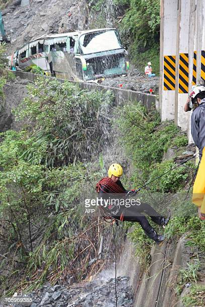 In a picture taken on October 22, 2010 rescurers search for trapped Chinese tourists from a convoy of buses caught in a mudslide caused by Typhoon...
