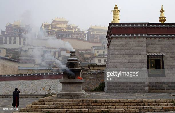 In a picture taken on September 14, 2013 a Tibetan woman prays after burning offerings at the Ganden Sumtsenling Monastery in Shangri-La, Diqing...
