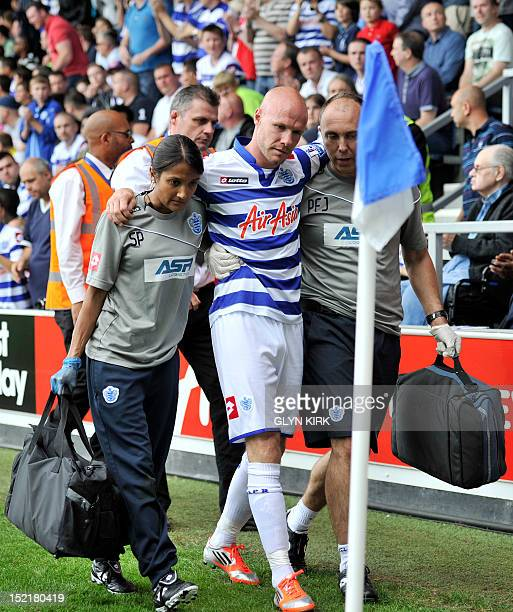 In a picture taken on September 15 2012 Queens Park Rangers' English striker Andy Johnson is helped off the pitch after injuring his knee during...
