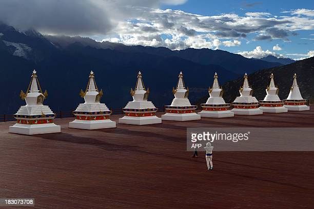 In a picture taken on September 19, 2013 a tourist poses for a picture in front of stupa's and the Meili snow mountain range in Deqen county, Diqing...