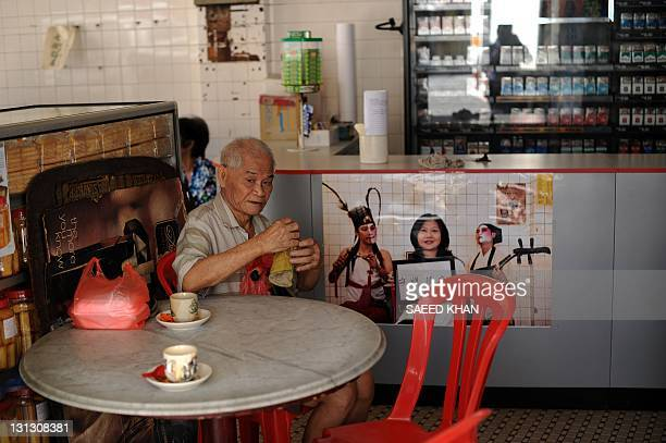 In a picture taken on September 29 a customer enjoys his tea inside a 70year old Lok Ann hotelin down town Kuala Lumpur This hotel and dozens of...