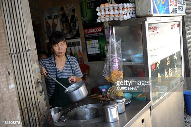 In a picture taken on September 29 a shopkeeper prepares noddles for a customer inside a shop of an old hotel in down town Kuala Lumpur This hotel...
