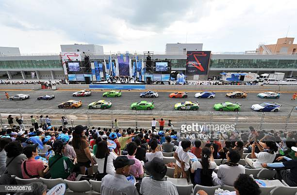 In a picture taken on September 4 2010 spectators watch a parade of racing cars on the track of the Korean International Circuit under construction...