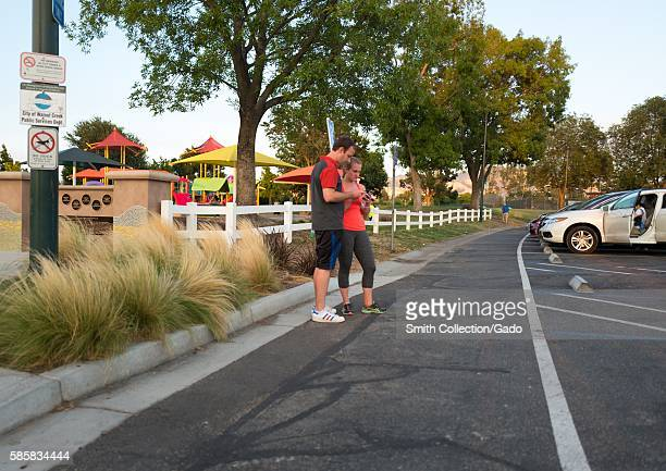 In a public park in the San Francisco Bay Area a couple use their smartphones to play the popular augmented reality game Pokemon Go July 2016