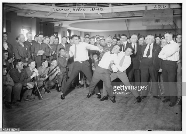 In a publicity photo boxer Jack Dempsey magician Harry Houdini and Benny Leonard stage a mock fight for soldiers 1920s