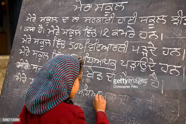 In a Punjabi rural school a young girl writes on school blackboard whilst other children look on in an open courtyard India   Location Chita Kalaan...