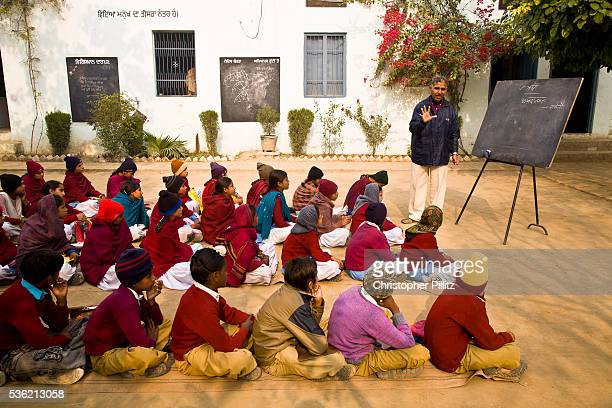 In a Punjabi rural school children take exams sitting on mats on the open ground of the school yard amidst the remnants of a cold misty winter...