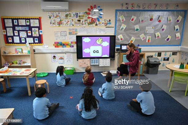 In a reception classroom children sit apart from each other on a carpet where crosses have been marked out for them to sit on in a teaching...