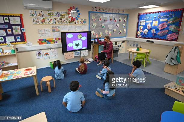 In a reception classroom, children sit apart from each other on a carpet where crosses have been marked out for them to sit on, in a teaching...