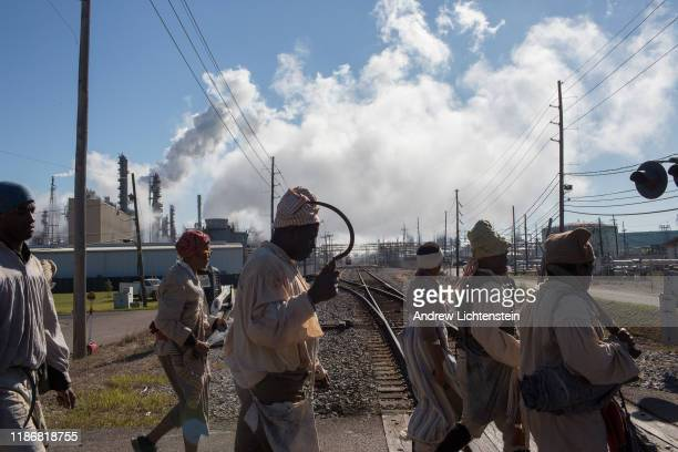 In a recreation of the 1811 German Coast slave rebellion reenactors march past a Shell oil refinery on their way to New Orleans on November 9 2019 in...