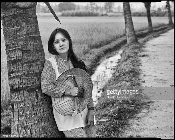 In a rice paddy near the village of My Lai, one of the survivors of the 1968 massacre there, Pham Thi Tranh, leans against a tree with her hat in her...