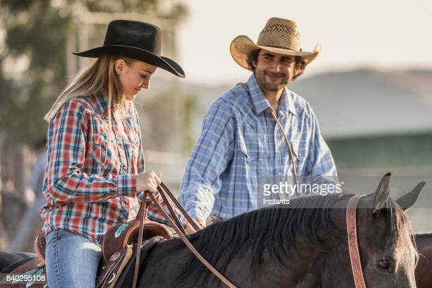In a rodeo arena, a young couple riding their horses before the action begins.