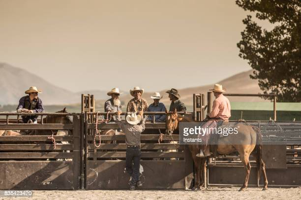 In a rodeo arena, cowboys just chilling out before the action begins.