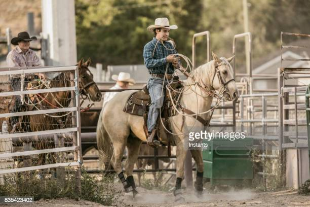 In a rodeo arena, two cowboys just chilling out before the action begins.