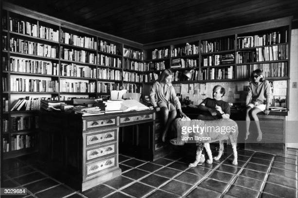 In a room lined with bookshelves Quintana Roo Dunne sits on a desk and pets a dog while her parents American authors and scriptwriters John Gregory...