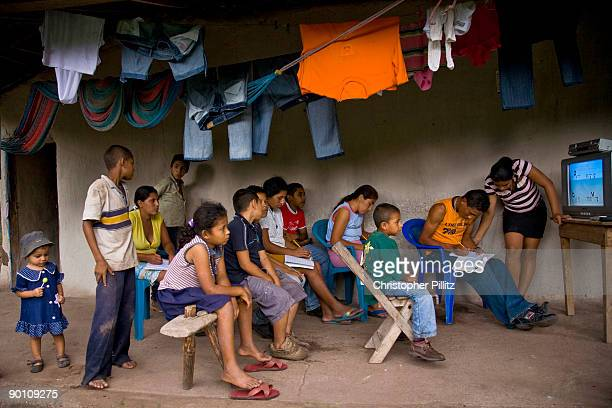 In a rural village jsut outside Jinotega Elena Alvarez teaches a group of children and adults the basic programme devised by the government to...