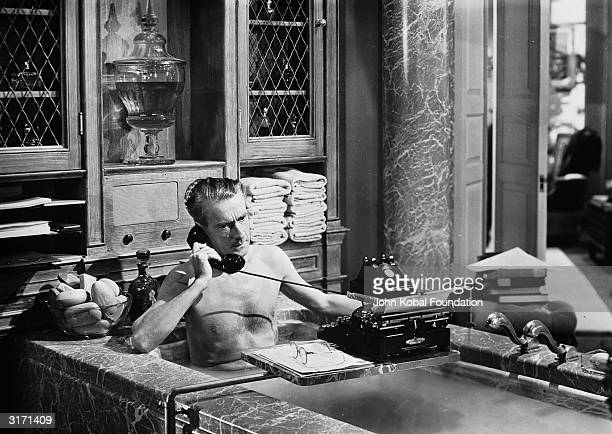 In a scene from the 20th Century Fox film noir 'Laura' directed by Otto Preminger Clifton Webb playing the character Waldo Lydecker takes a telephone...