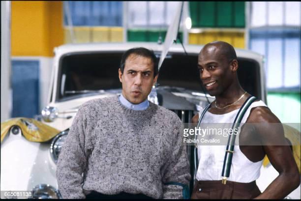 In a scene from the movie 'Lui e peggio di me' directed by Enrico Oldoini actor Adriano Celentano talks to a black man in a garage with a white...