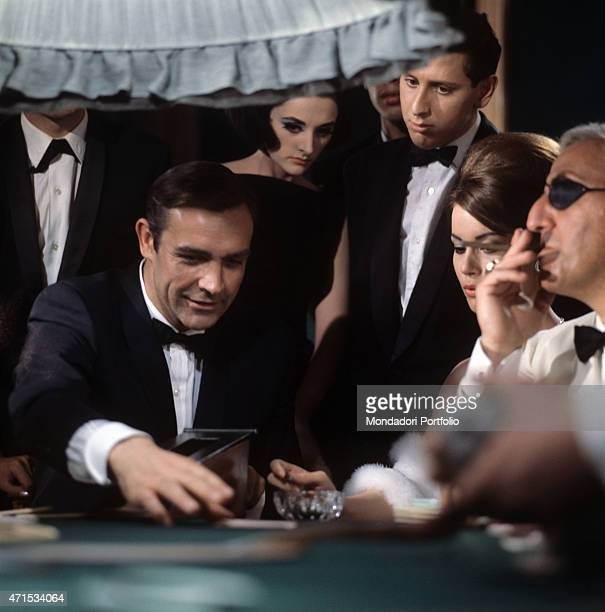 'In a scene of Thunderball the actor Sean Connery in the guise of MI6 agent James Bond has just won a hand at Baccarat at the gambling table under...