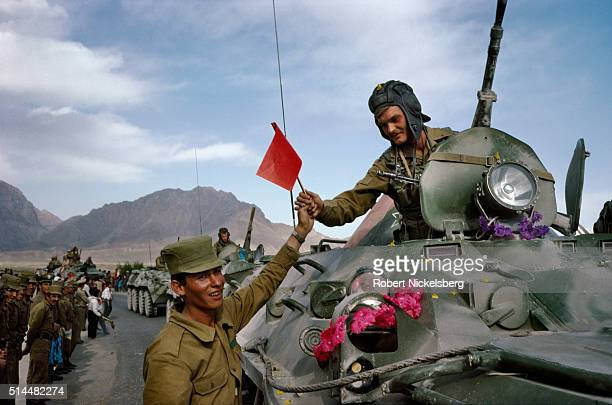 In a show of solidarity an unidentified Afghan soldier hands a flag to a member of a Soviet tank on the first day of the Soviet army's withdrawal...