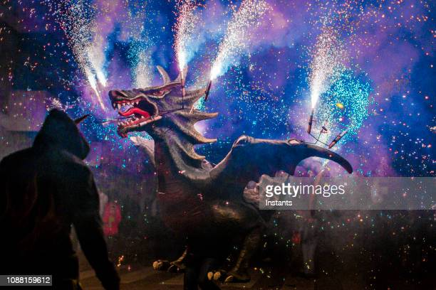 in a small catalan village, traditional festival, called correfoc which means running fire, being held where people form a parade, disguised as devils and other creatures while fireworks light up the street. - devil costume imagens e fotografias de stock