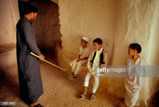 In a small street a man calms children down with a stick April 2000 in Ghadames Libya
