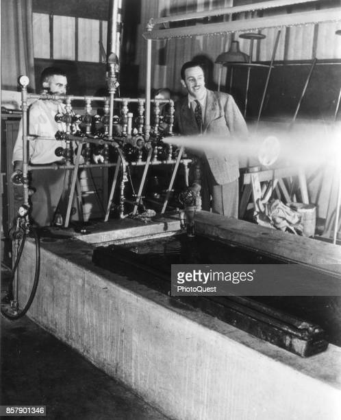 In a sound effects studio American movie producer artist and animator Walt Disney watches as a machine uses steam to produce a whistle blast sound...
