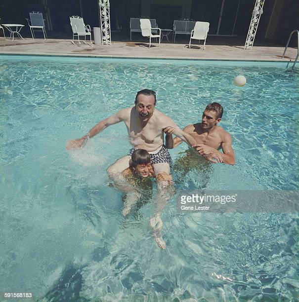 In a swimming pool American movie producer artist and animator Walt Disney gets a piggy back ride from one of his daughters 1950s