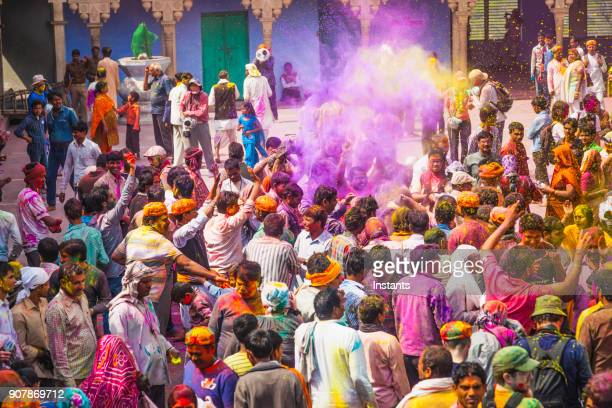 In a temple outdoor part, of Mathura district, the crowd is celebrating Holi festival.