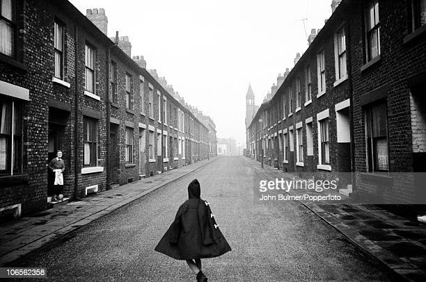 In a town in the north of England, a woman watches from her doorway as a boy walks down the street of terraced houses wearing his duffel coat like a...
