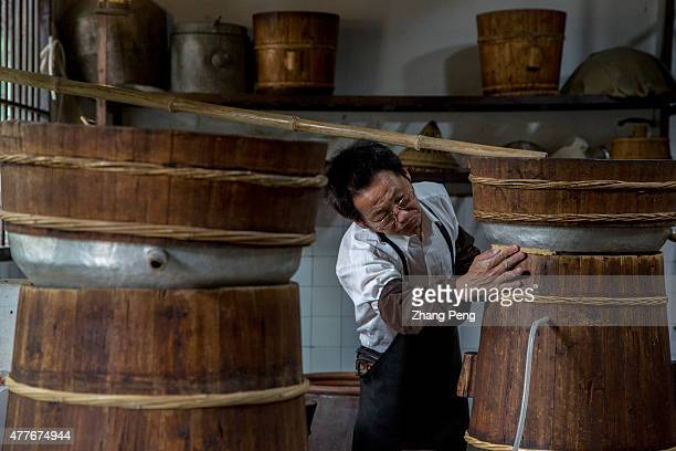 In a traditional workshop a craftsman is making distilled liquor In local tradition people often make distilled alcohol with excess fermented rice...