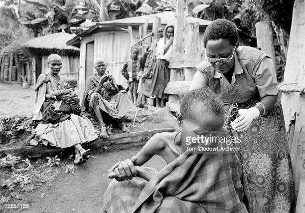 In a village near Arusha Tanzania community nurse Paulina Natema attends to a Maasai woman who has contracted HIV/AIDS It is estimated that 254...