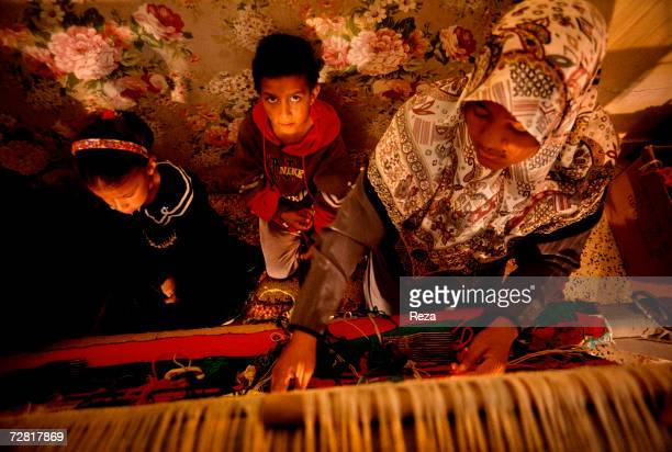 In a weaving workshop a woman weaves a carpet with her children by her side April 2000 in Ghadames Libya