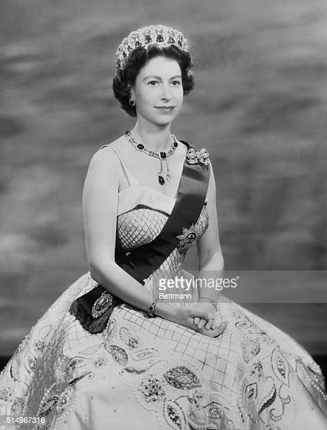In a white satin evening gown embroidered in gold and pearls Queen Elizabeth is shown in this royal command portrait She wears the Rib and Star of...