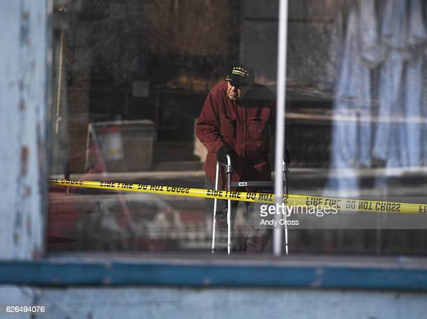 In a window reflection owner of the Green Door Furniture store Al Stewart looks over his store which was heavily damaged in a fire earlier in the...