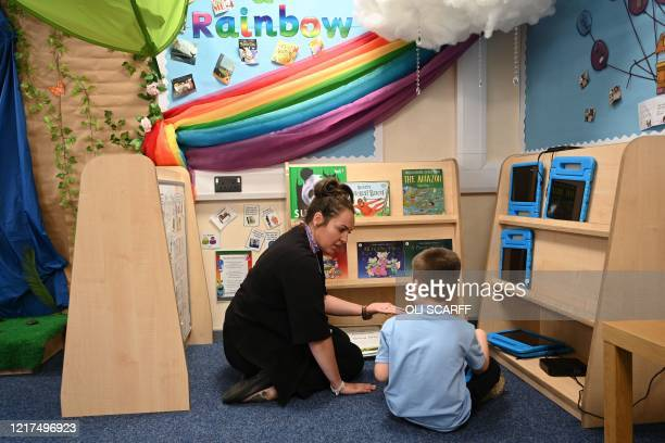 In a year 1 classroom, Hayley Walker speaks with a boy in a teaching environment safe from Coronavirus for pupils and teachers at Brambles Primary...