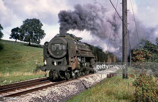 CONTENT] In absolutely filthy condition Britannia 70018 Flying Dutchman thunders past at Thrimby Grange on a van train on 13/9/66 70018 was withdrawn...